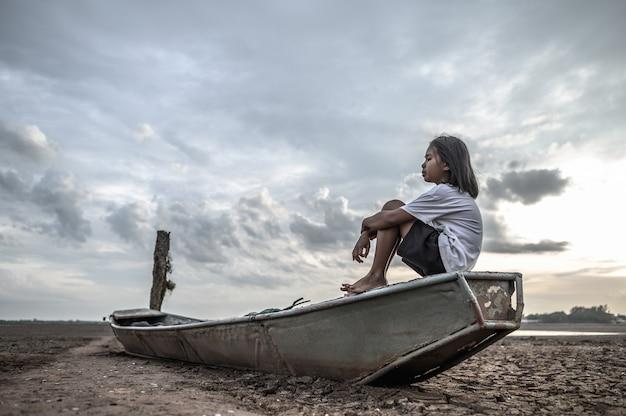 女性は漁船でひざを抱いて座り、乾燥した土地と地球温暖化の空を見る