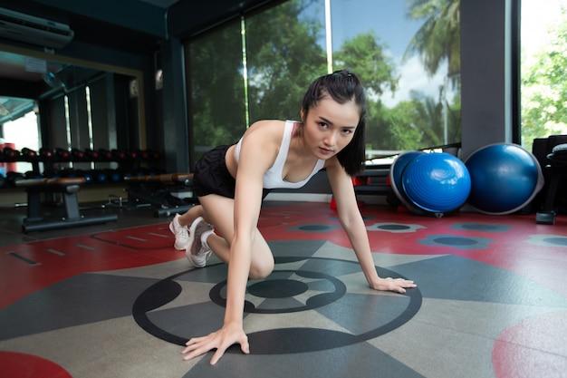 若い女性は、運動する前に床を押してジムで膝を曲げてウォームアップします。