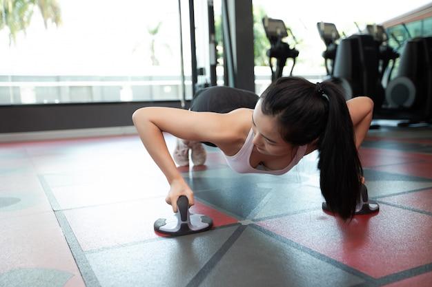 ジムのフィットネスプッシュアップスタンドで床を押して運動する女性