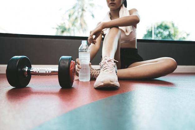 女性は運動後、座ってリラックスします。水筒とダンベルがあります。