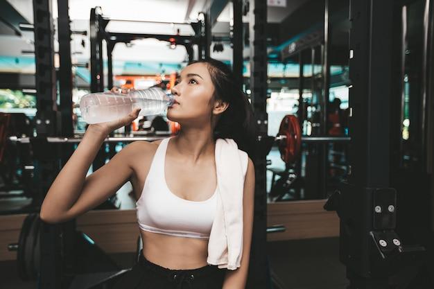 運動後の女性は、ジムでボトルやハンカチから水を飲みます。