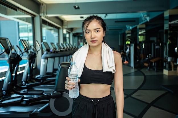 女性が立って、運動後にリラックスし、水のボトルを保持しています。