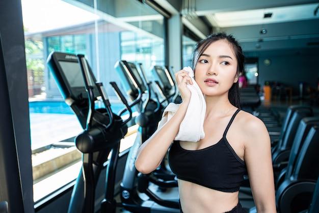 運動後の女性は、ジムで白い布で顔を拭いてください。