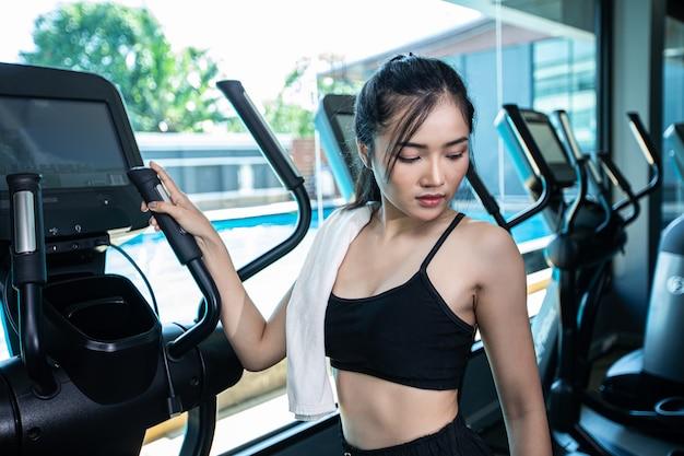 Красивые фитнес женщины готовятся к бегу на беговой дорожке в тренажерном зале.