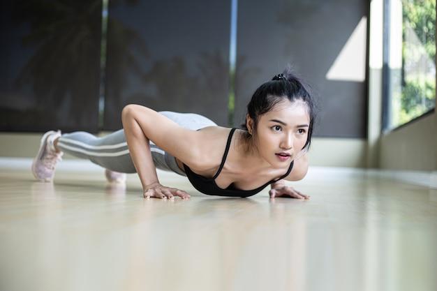 ジムで床を押して運動する女性