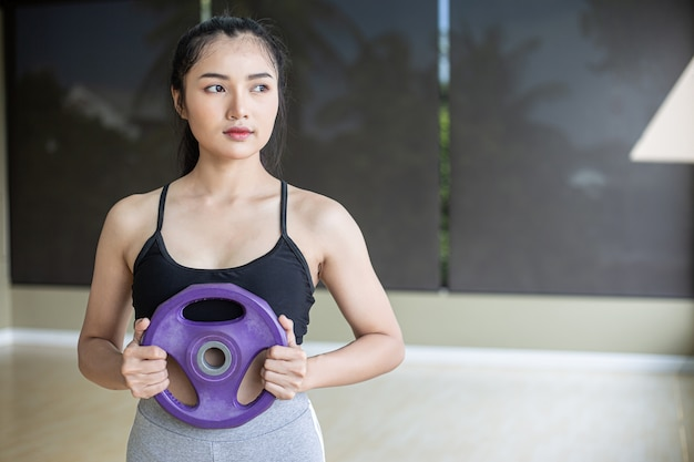 女性は胸にダンベルウェイトプレートを装着して運動します。