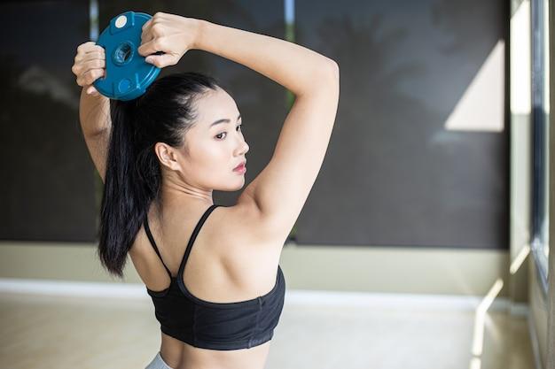 女性はダンベルのウェイトプレートで運動し、背中をひねります。