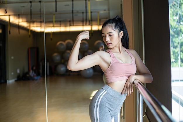 フィットネス女性は、ジムで腕の筋肉を見せます。