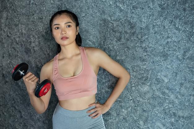 ジムで赤いダンベルで運動に立っている女性。
