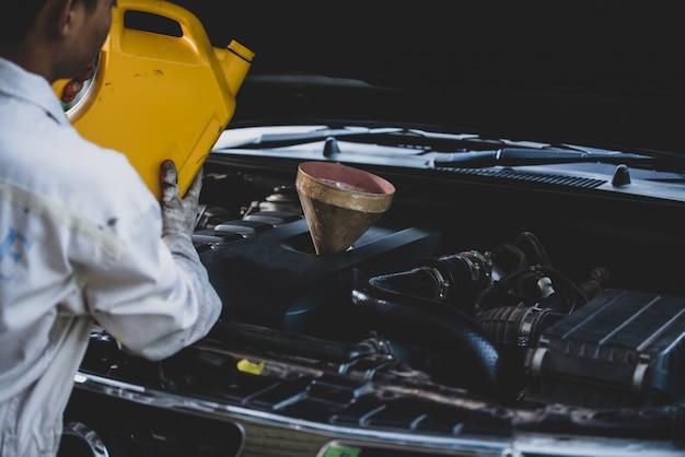 自動車修理工のガレージで車のエンジンに新鮮なオイルを注いで交換する自動車整備士の手を閉じます。自動車整備と産業コンセプト