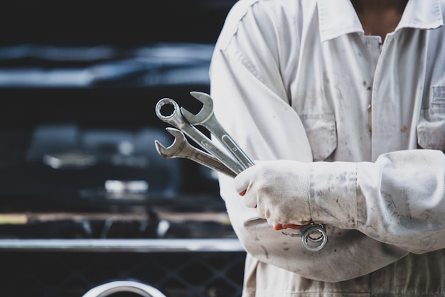 白い制服を着て、メカニックにとって不可欠なツールであるレンチを保持している車の修理工