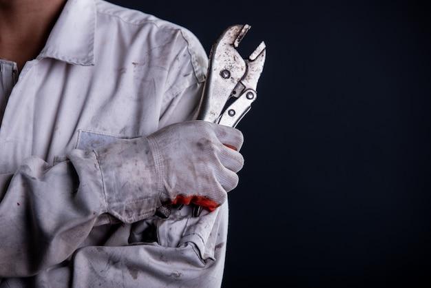 レンチを保持している白い制服スタンドを着て自動車修理工
