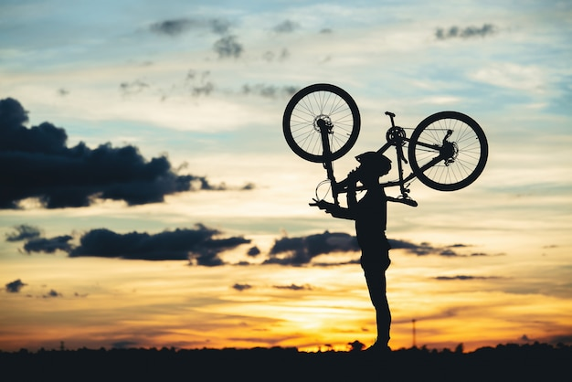 日没時のシルエットを休んでサイクリスト。アクティブな屋外スポーツコンセプト