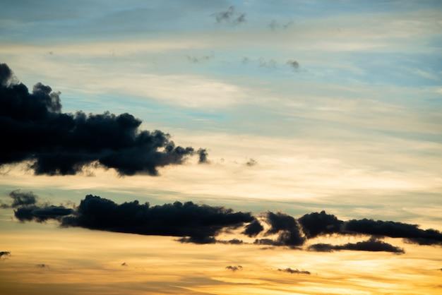 フィールドまたは草原の自然日没の日の出。明るい劇的な空と暗い地面。