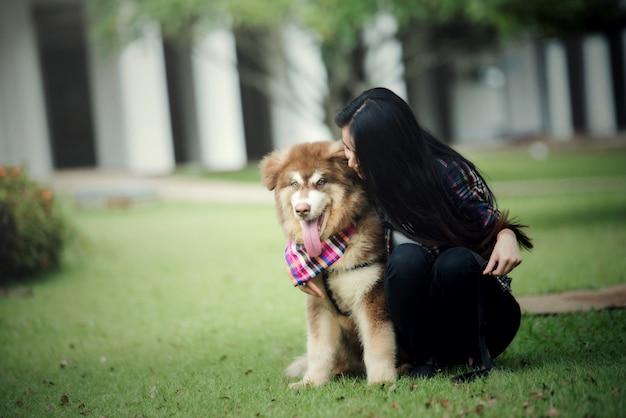 屋外の公園で彼女の小さな犬と遊ぶ美しい若い女性。ライフスタイルの肖像画。