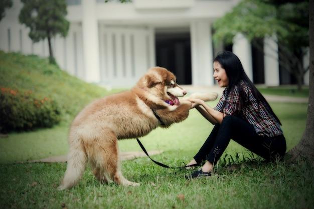 Красивая молодая женщина, играя со своей маленькой собакой в парке на открытом воздухе. образ жизни портрет.