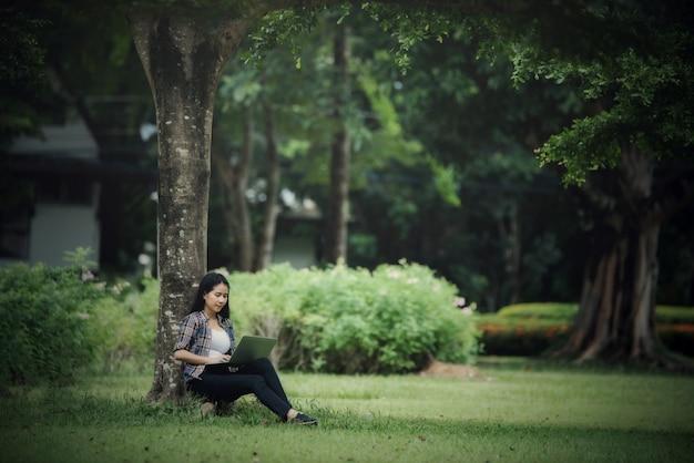 屋外の公園で本を読んで美しい若い女性
