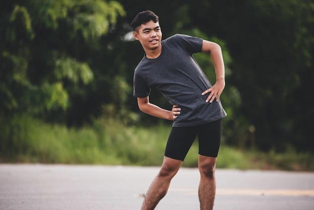 Мужской бегун делает упражнения на растяжку, подготовка к тренировке