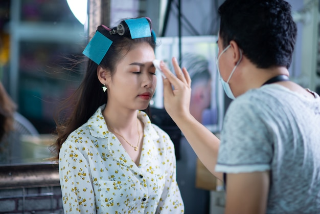 Женский парикмахер, стоя, макияж лица и прическа для милой милой молодой женщины в салоне красоты