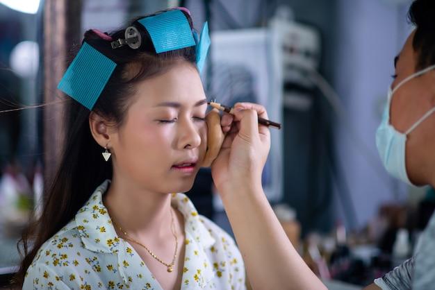立っている女性の美容師、顔メイクと美容院でかわいい素敵な若い女性に髪型を作る