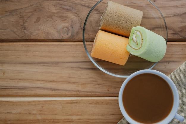 茶色の木の床に置かれたコーヒーとパン。