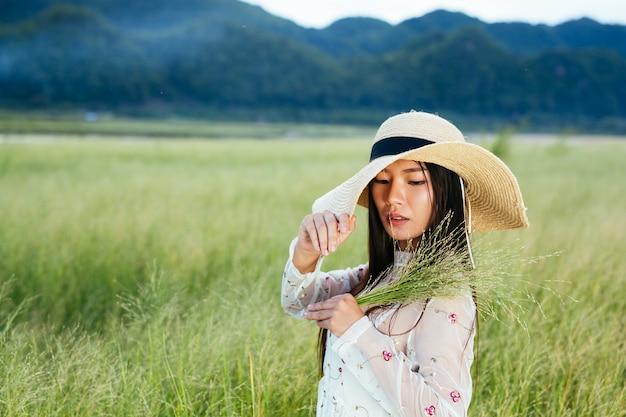 山のある美しい草原で手に草を持っている女性。