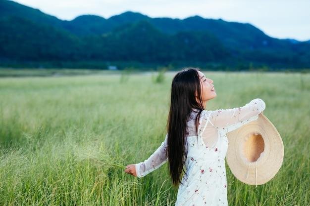 美しい幸せな女性が帽子を美しい草原に投げており、山に山があります。