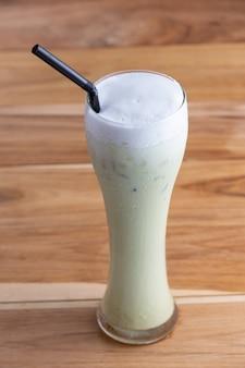 板の床に置かれた背の高いグラスに入れた冷たい緑茶。