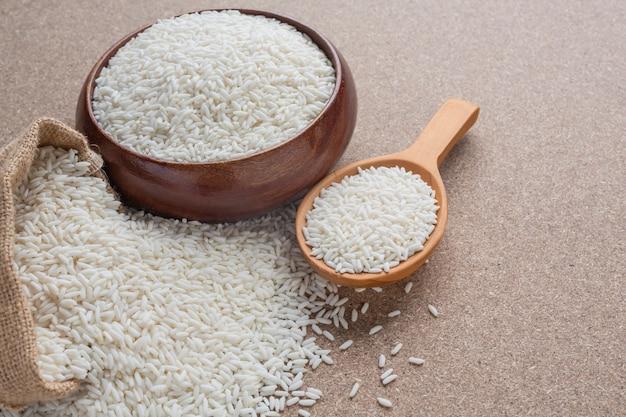 Зерно, которое находится в чашке на деревянном полу.