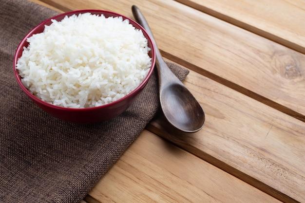 Приготовленный рис в красной чашке ставят на фанерный пол.