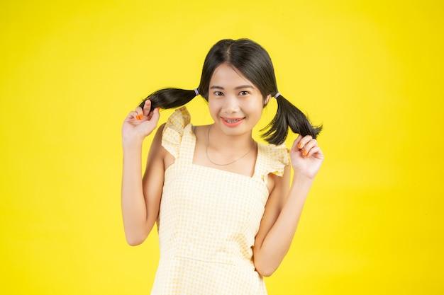 Красивая женщина, которая счастлива, показывая различные жесты на желтом.