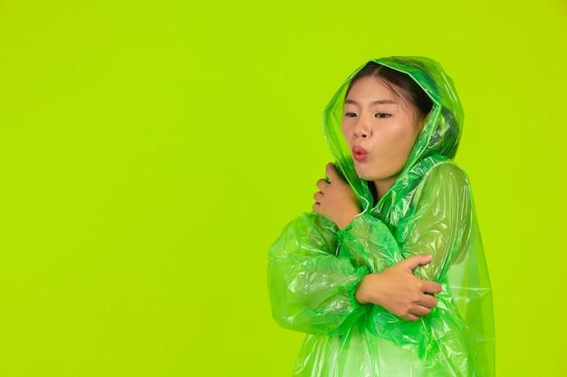 Счастливая красивая девушка, нося зеленую одежду, зонтик и пальто, дождливый день.