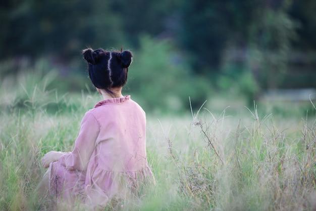 フィールドに座っている若いヒッピーの女の子。