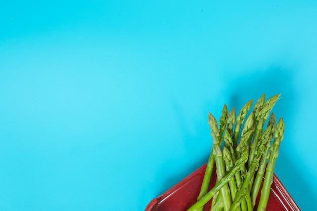 Зеленые овощи помещены в лоток с синим цветом.