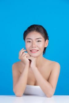 Красота женщины с идеальным здоровьем кожи изображения касаясь ее лица и улыбаясь, как спа, чтобы побаловать ее кожу синий