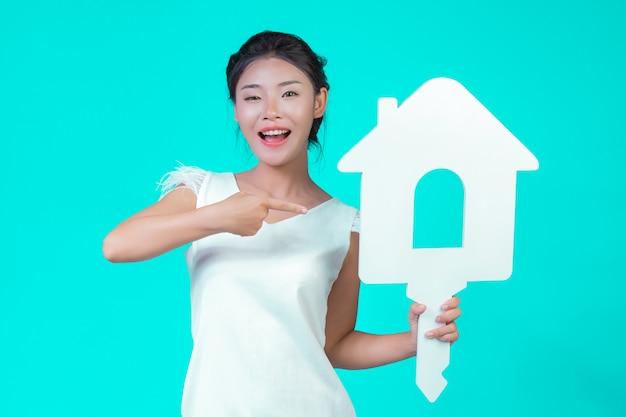 Девушка была одета в белую рубашку с длинными рукавами с цветочным рисунком, держала символ дома и показывала различные жесты синим цветом.