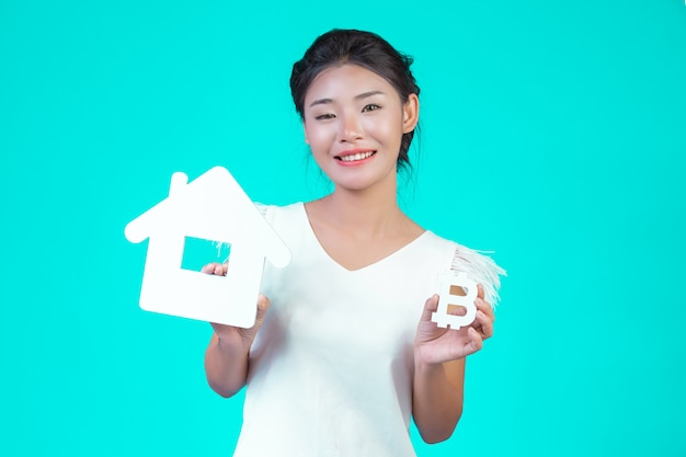 若い女性は花柄の白い長袖のシャツを着て、家のシンボルを保持し、青の通貨シンボルを保持していました。