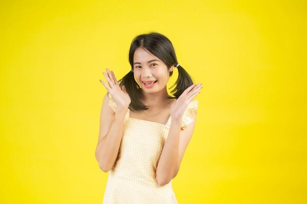 黄色に色々なジェスチャーを見せて幸せな美しい女性。