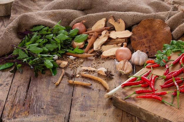 アジア料理を作るために使用されるさまざまな材料が木製のテーブルに置かれています。