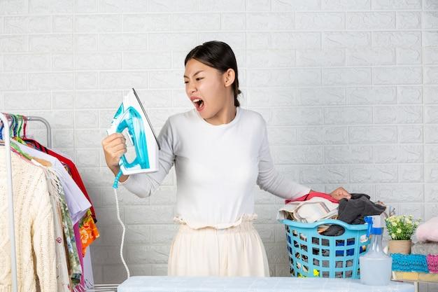 Домработница, которая расстроена своими утюгами с белым кирпичом.