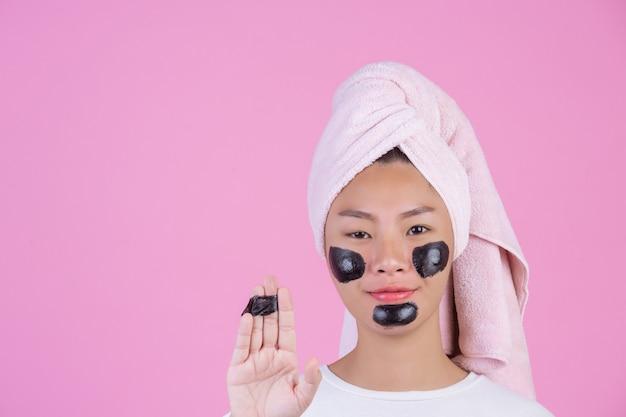 Косметический косметический пилинг. молодая самка с черной отшелушивающей маской на коже косметический уход за кожей пилинг продукт на лице на розовый.