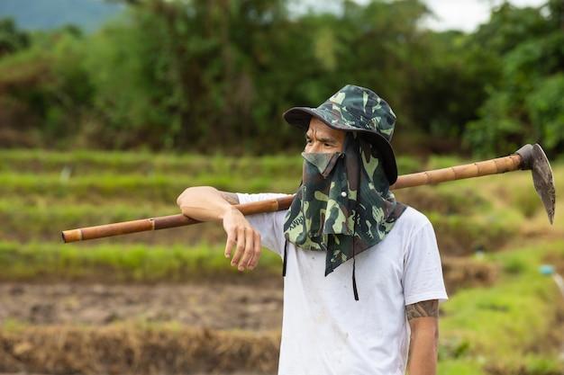 彼の田んぼを見ている若い農夫。