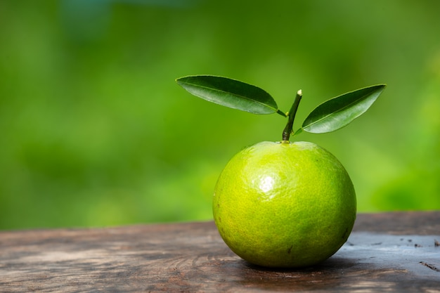 Плод апельсина размещен на деревянном полу и имеет натуральный зеленый цвет.