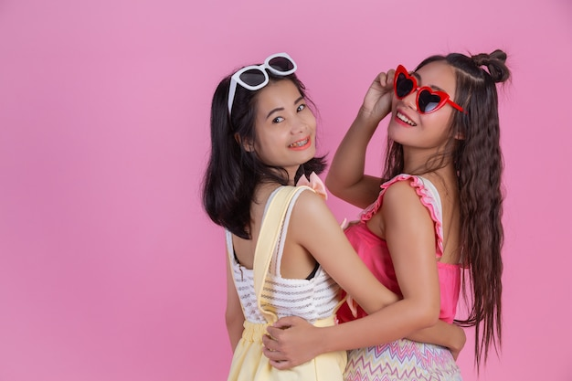 Две азиатские подружки счастливы и имеют розовый.