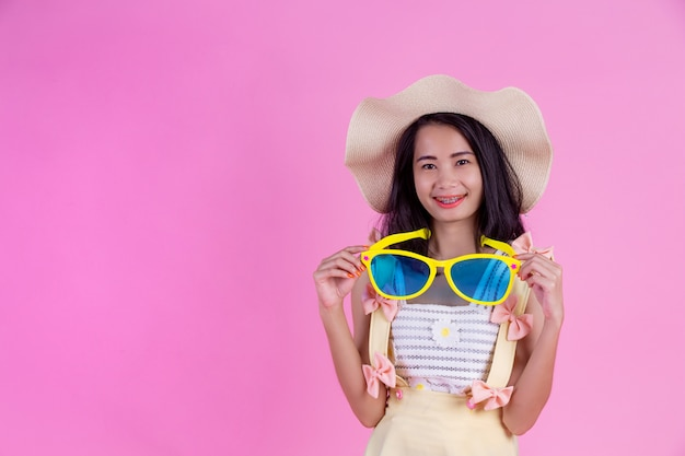 ピンクの帽子と大きな眼鏡をかけている美しいアジアの女性。