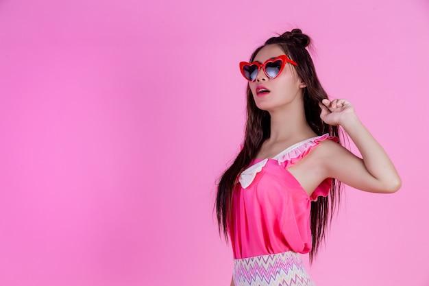 Красивая женщина в красных очках с большой шляпе на розовый.