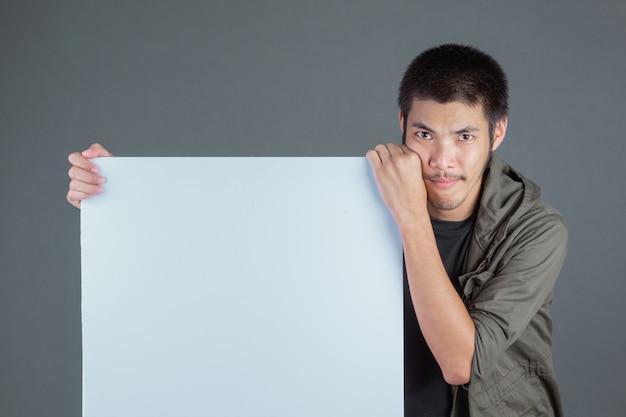 灰色の白いラベルの側に立って、濃い緑色のシャツを着た短髪の男。