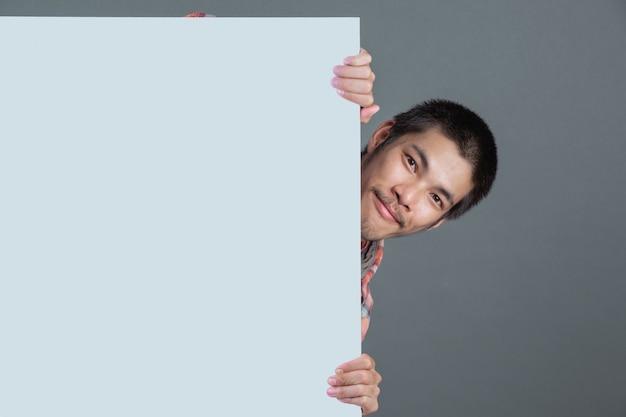 赤い格子縞のシャツを着た短髪の男は、灰色の白いラベルで立っています。