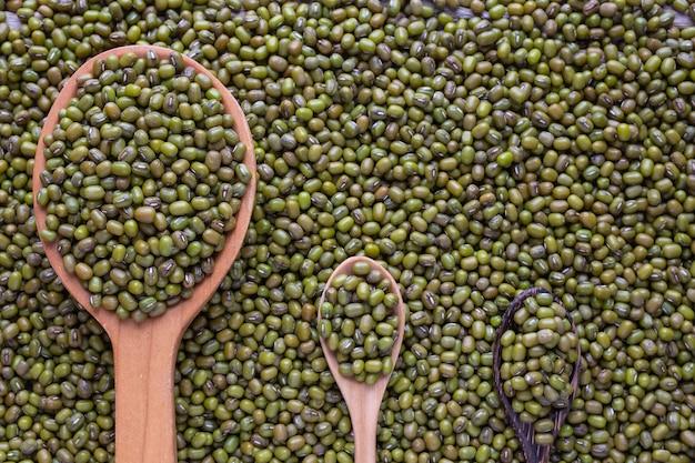木製の床に置かれたカップに生の緑豆。