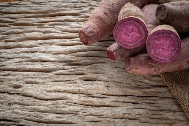 茶色の木製の床に置かれた紫色のサツマイモ。